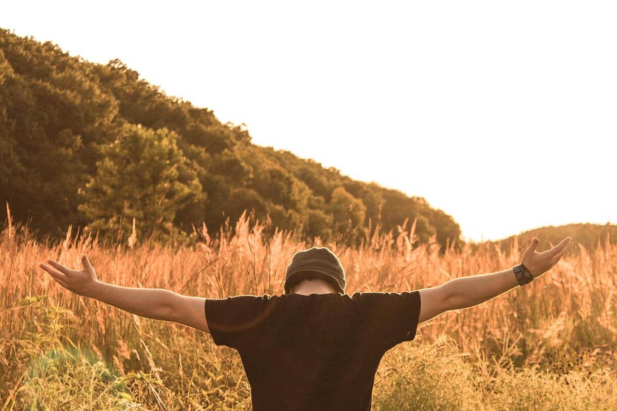 Picture of a man in a field facing away from us with arms stretched wide.