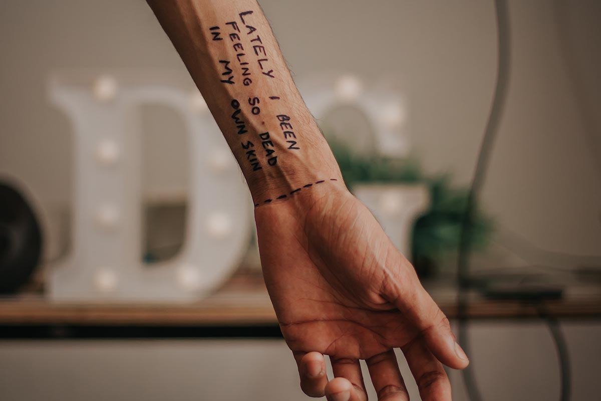 This image is of a forearm with writing and it expresses hidden pain.